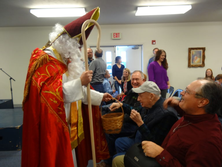 saint-nicholas-handing-out-treats-to-adults